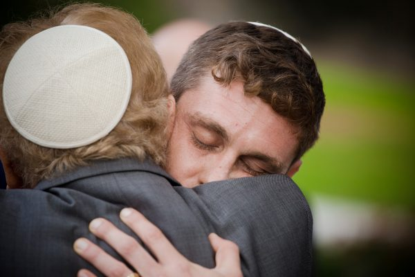 Groom gives grandpa a hug at La Jolla Jewish wedding