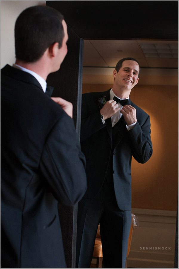 Groom getting ready fixing tie in mirror at san Diego wedding