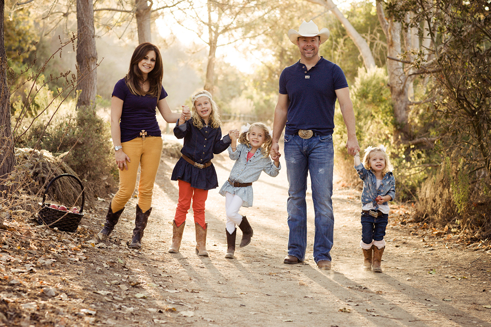 family with kids having their holiday photo session on a San Diego nature trail wearing cowboy boots