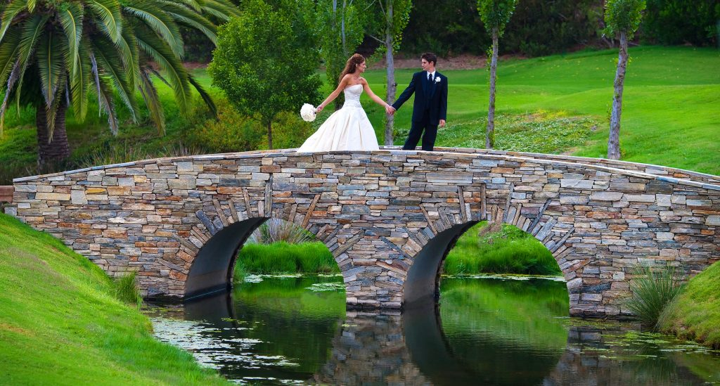 bride and groom holding hands as they cross a bride at a rancho Santa Fe golf club