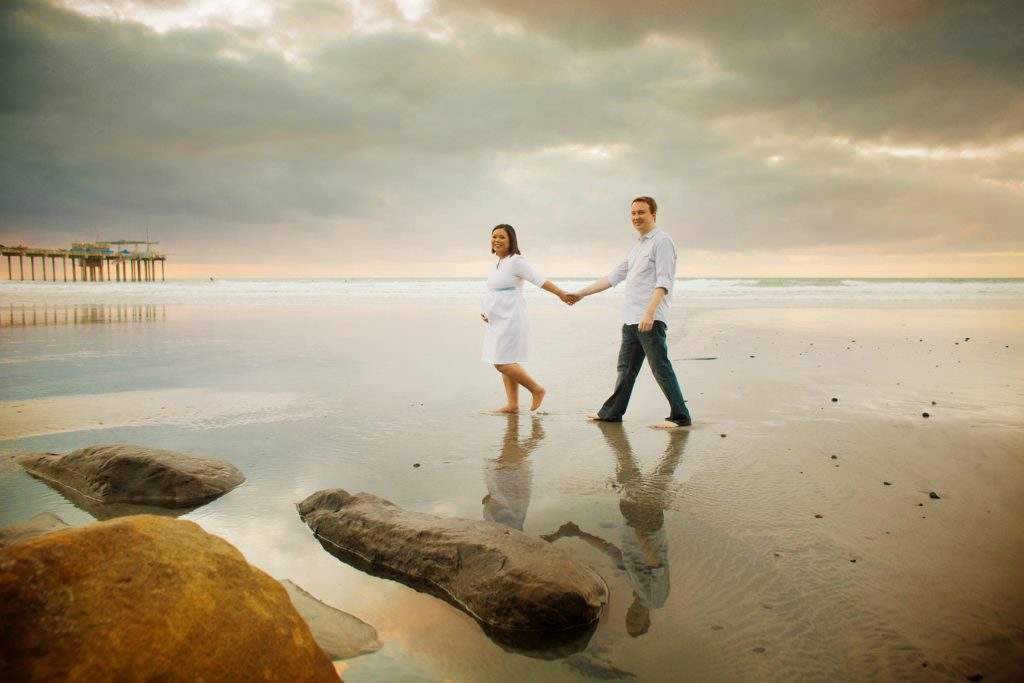 happy couple stroll on the beach at sunset during their maternity shoot holding hands and so excited to be parents .