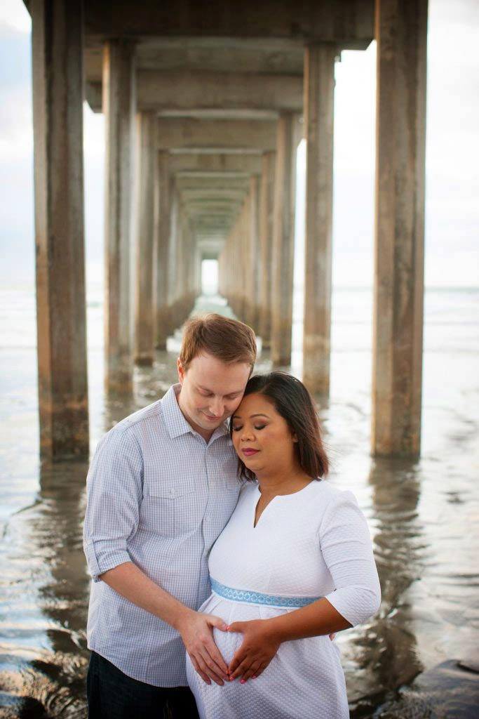 couple enhance as they pose for their happy maternity portrait it's a girl by Dennis mock photography in San Diego
