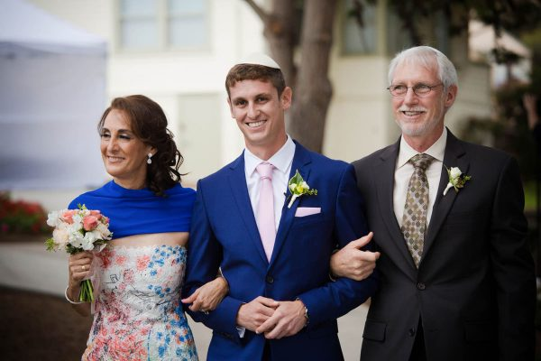 Groom is escorted by his parents down the wedding aisle at La Jolla Scrips cottage