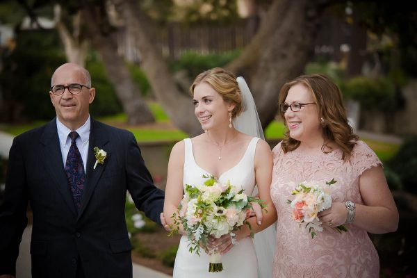 Bride walks down the aisle with parents and eyes the groom at La Jolla scripps cottage wedding