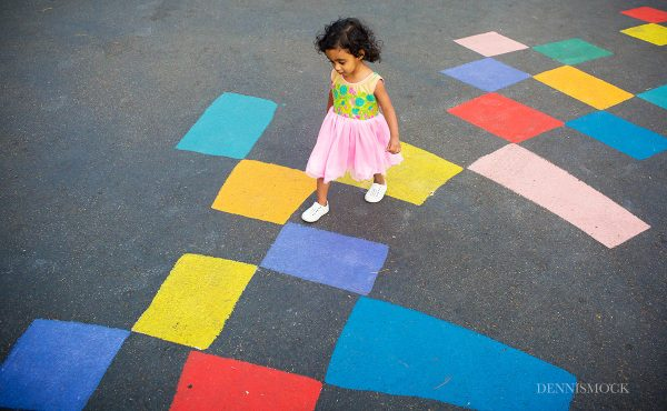 little one year girl skipping colorful playground during a San Diego Family portrait session by documentary photographer Dennis mock