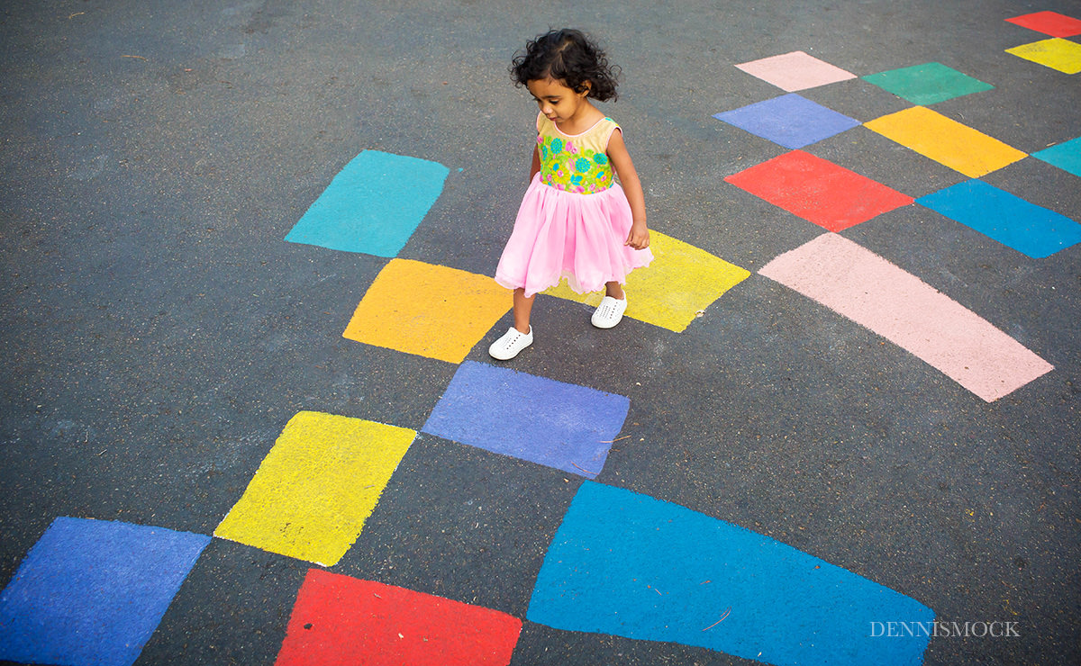 playful fun moment captured with little girl hopping in Balboa Park family