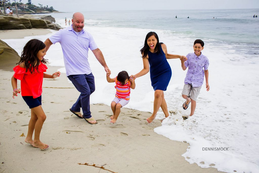 jumping the waves at windeansea beach La Jolla during a family beach portrait session. photo credit Dennis mock family photographer