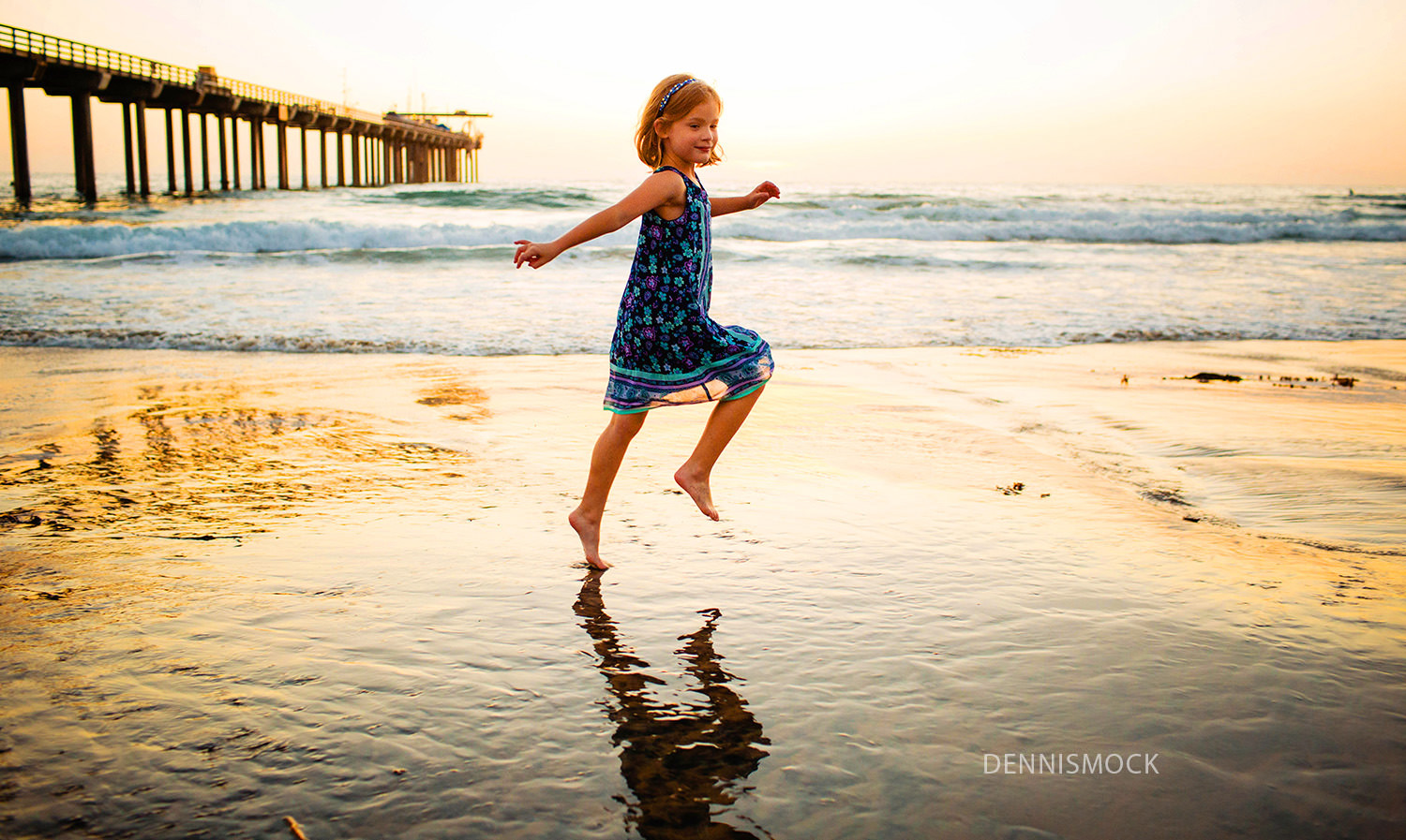 Little girl dancing at La Jolla sunset skipping the waves at photo session
