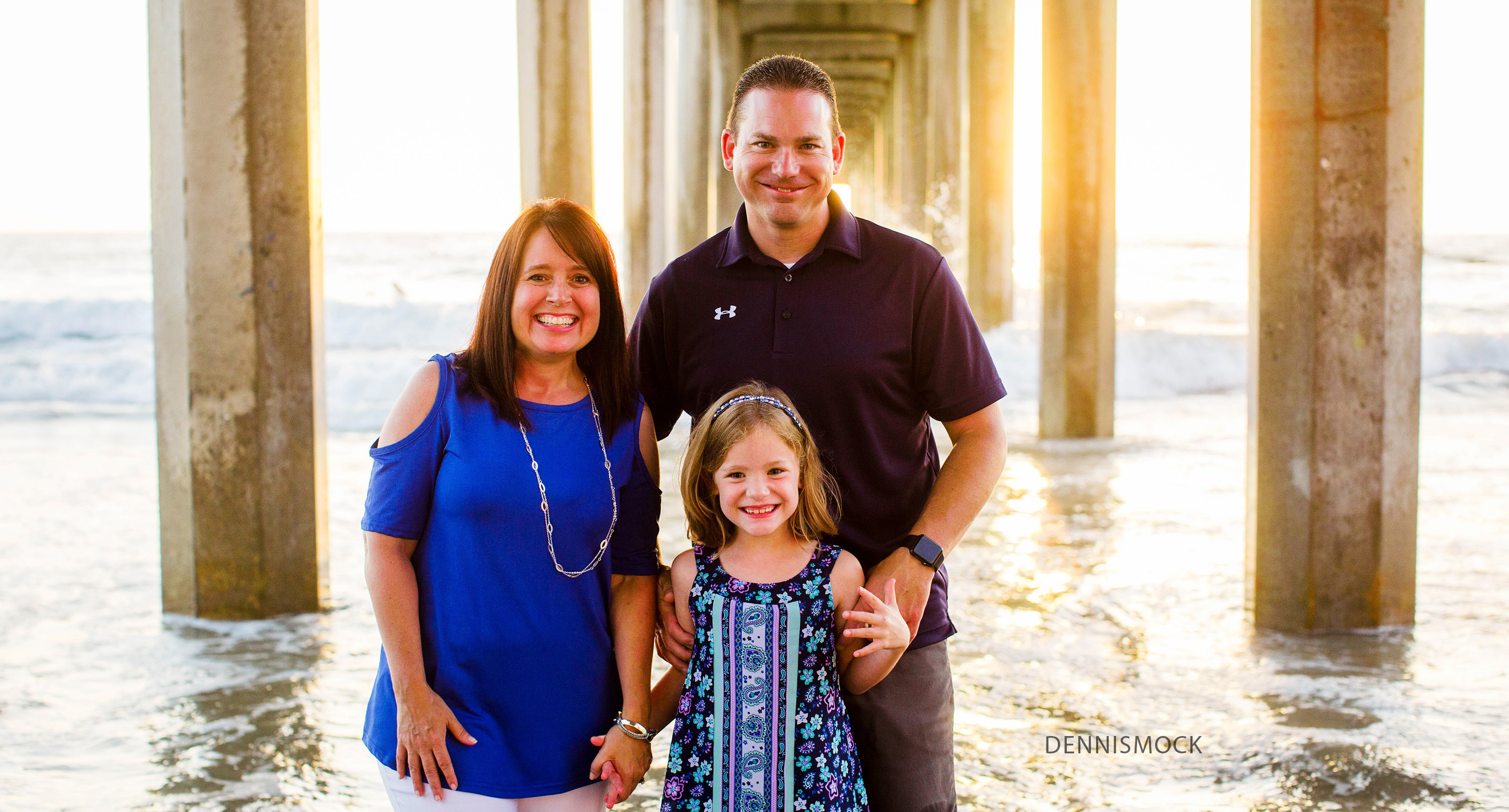 Colorful family portrait at sunset captured at sunset under the pier. Photo by San Diego photographer Dennis mock