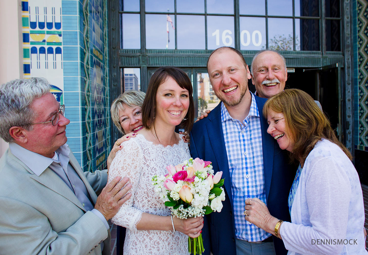 wedding couple receives congrats and hugs from loving parents outside the San Diego courthouse