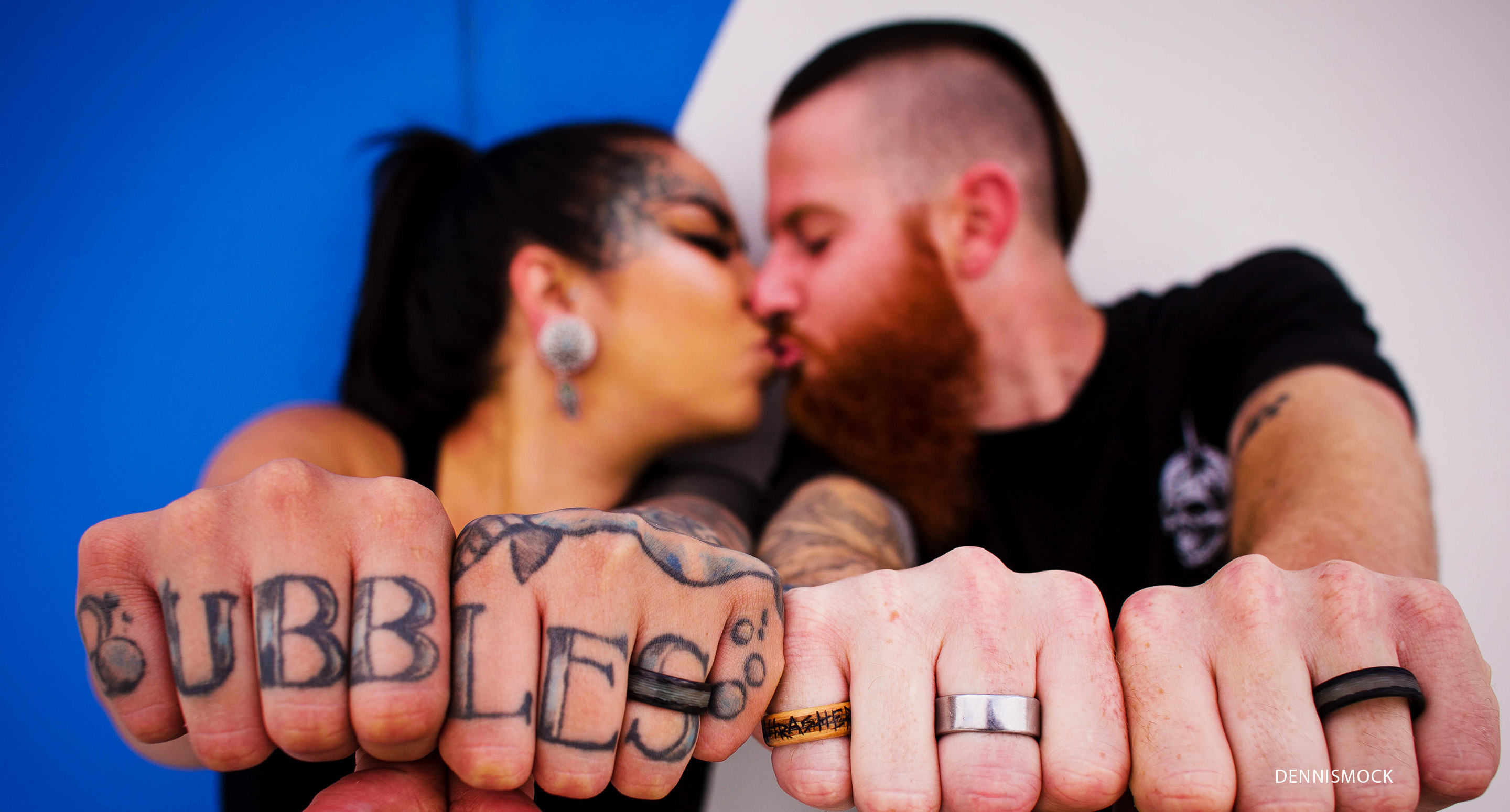 The power of a kiss. Couples showing off their ink during engagement photo session in downtown San Diego. Photo credit Dennis Mock photographer
