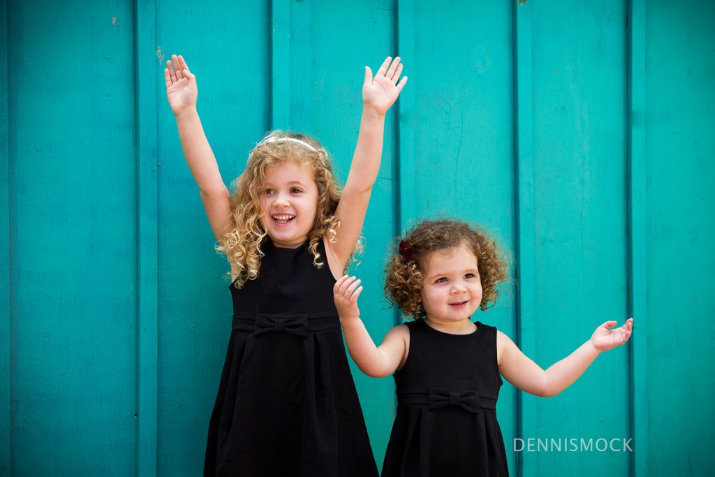 sisters having fun during a family portrait session in Balboa park. Photo by Dennis mock in Spanish Village Art Center