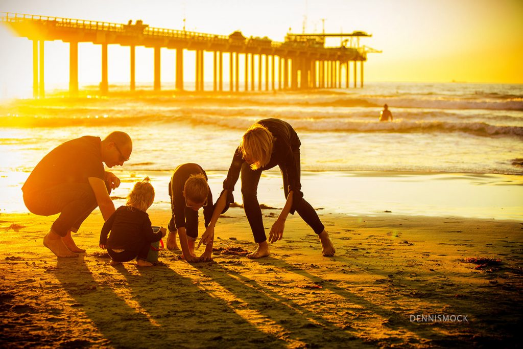 Parents helping the kids dig a sand castle with La Jolla Scripps Pier in the background during a documentary family portrait shoot with Dennis Mock Photographher