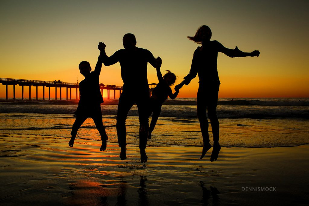 San Diego family playing in the surf and sandcastles at La Jolla scripps pier . Photo by Dennis Mock Photography