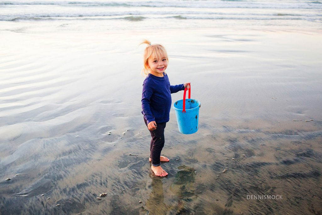 little girl playing in the surf at La Jolla scripps pier on a San Diego family portrait session by Dennis mock photographer