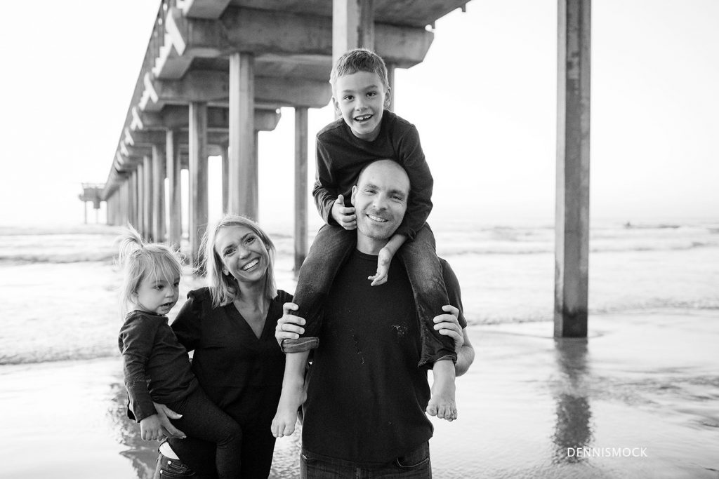 Black and white image of family enjoying time together during a family portrait session in La Jolla