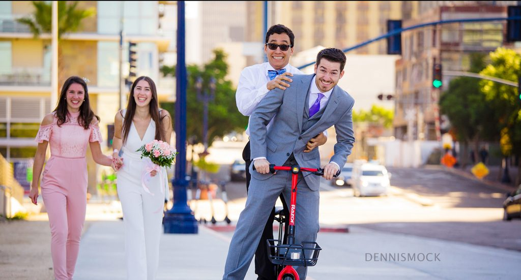 fun couple ride scooter to their downtown San Diego courthouse wedding . Photo by Dennis Mock Photography