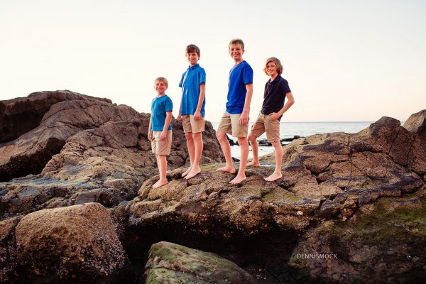 cousins pose on rocks on the La Jolla scripps pier during a family beach portrait session. Image by Dennis Mock Photographer