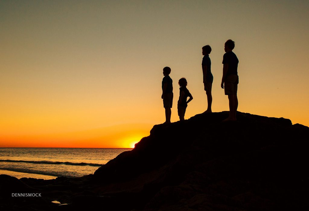 cousins climb the rocks during a family beach portrait session to watch for the green flash . Image by Dennis Mock Photographer