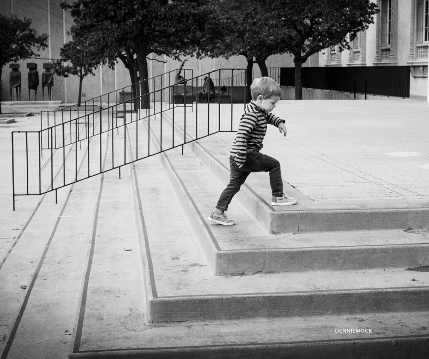 little boy running up the steps at the Balboa Park Art museum in black-and-white classic look