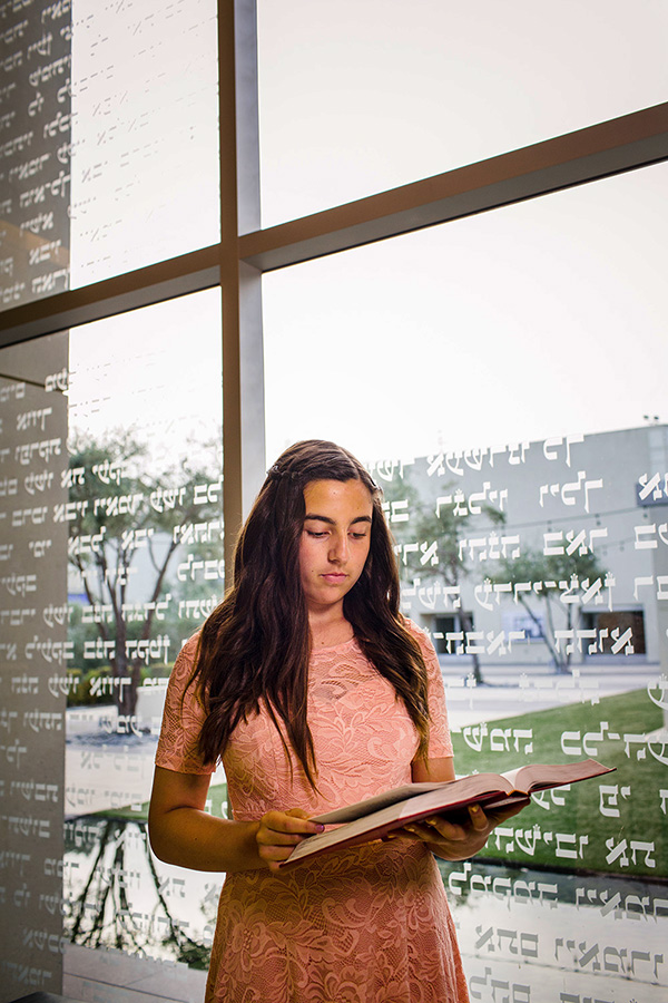 Bat mitzvah portrait of girl reading book before her service in La Jolla